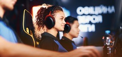 Side view of a happy mixed race girl, female cybersport gamer wearing headphones playing online video games and smiling, participating with professional team in tournament
