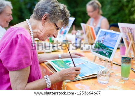 Side view of a happy senior woman smiling while drawing as a recreational activity or therapy outdoors together with the group of retired women. #1253664667