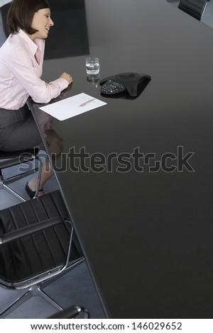 Side view of a happy young businesswoman with calculator and document at conference table