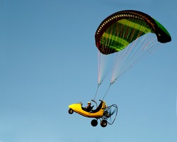 Side view of a high flying paraglider in a solid blue sky.