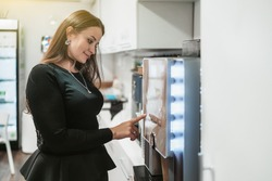 Side view of a hispanic woman with long hair choosing what type of coffeedrink to prepare using a coffee machine maker while standing indoors of a cozy office kitchen during a break