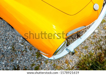 Side view of a hood of a yellow classic car