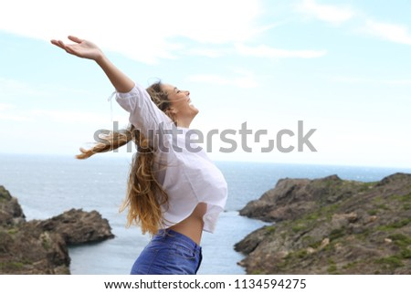 Side view of a joyful girl raising arms to the wind on a coast landscape