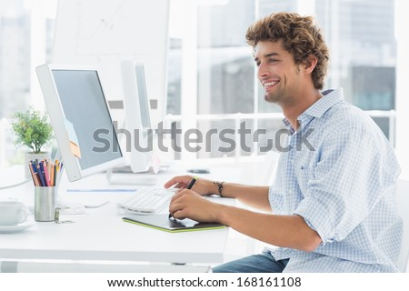 Side view of a male artist drawing something on graphic tablet with pen