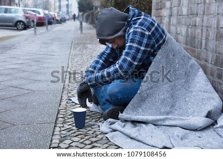 Side View Of A Male Beggar Sitting On Street Near Disposable Cup