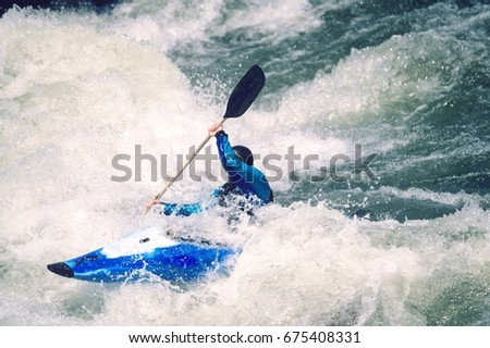 Side view of a male kayaker paddling through white water rapids
