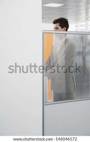 Side view of a male office worker standing behind cubicle wall in office