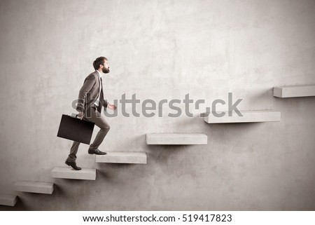 Side view of a man climbing the stairs built in a blank concrete wall. Concept of success and achieving your goal. Mock up #519417823