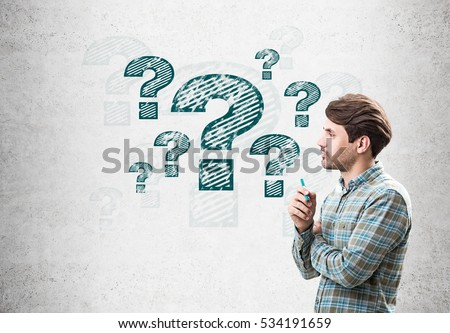 Side view of a man holding a marker and standing near a concrete wall with blue question mark sketches on it. Concept of problem solving #534191659