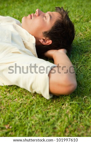 Side view of a man lying in grass with his eyes closed and his hands resting underneath his head