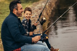 Side view of a man sitting on the banks of a lake and fishing with his kid. Close up of a man winding the reel of his fishing rod while his son looks at him.