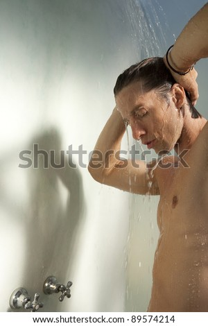 Side view of a man taking a shower.