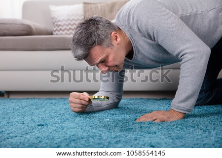 Side View Of A Mature Man Looking At Blue Carpet Through Magnifying Glass