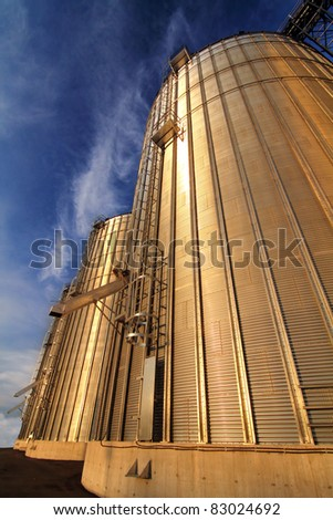 Side view of a modern metal silo at sunset