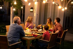 Side view of a multi-generation Caucasian family sitting outside at a dinner table in the evening for a celebration meal together, talking and eating