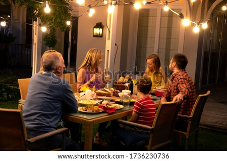 Side view of a multi-generation Caucasian family sitting outside at a dinner table in the evening for a celebration meal together, talking and eating Foto d'archivio ©