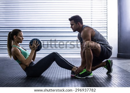 Stock Photo Side view of a muscular couple doing abdominal ball exercise