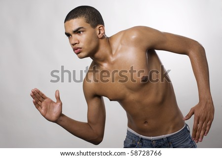 Side view of a muscular young man running in studio