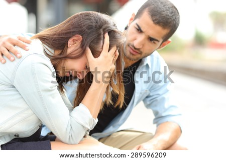 Side view of a muslim man comforting a sad caucasian girl mourning in a train station