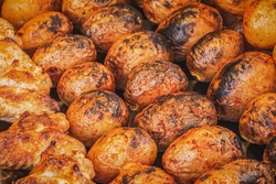 Side view of a potato baked to a golden crust. Fried potatoes on skewers on a charcoal grill in a street market. Appetizing tasty baked potato with spices with shallow depth of field