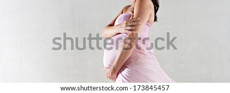 Side view of a pregnant woman body figure wrapped in pink silk floating fabric, holding her belly with care against a spacious plain background. Interior beauty pregnancy portrait.