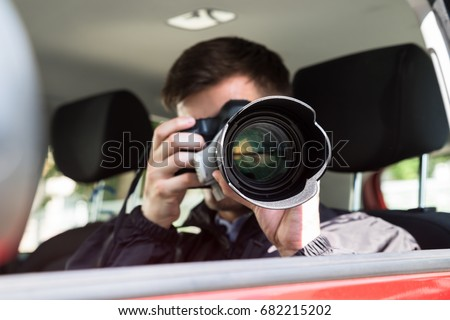 Side View Of A Private Detective Sitting Inside Car Photographing With Slr Camera