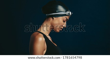 Side view of a professional female swimmer with goggles and a hat. Woman wearing black swimsuit, swimming cap and goggles on dark background looking exhausted.