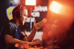 Side view of a professional male cybersport gamer wearing headphones talking by microphone with team member while playing online video game