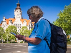 Side view of a relaxing senior woman with map standing in front of New Town Hall in Leipzig