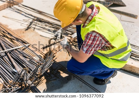 Side view of a reliable worker checking the quality of the steel bars, before using them for the reinforcement of the structure of a building under construction