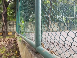Side view of a rusty green fence in a tennis court area in Jakarta in the morning
