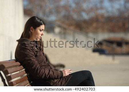 Side view of a sad pensive woman smoking sitting in a bench in the street in winter