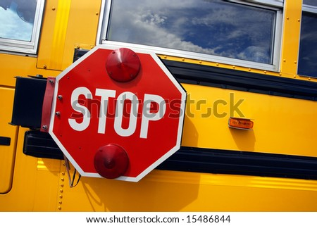 Side view of a school bus and its stop signal.