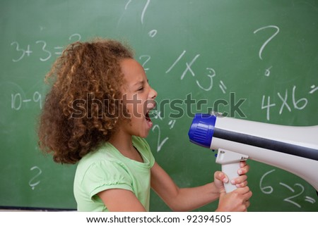 Side view of a schoolgirl screaming through a megaphone in a classroom
