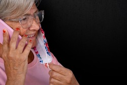 Side view of a senior woman using mobile phone smiling and taking off the surgical mask due to coronavirus. Portrait of elderly retired enjoying technology.  Black background