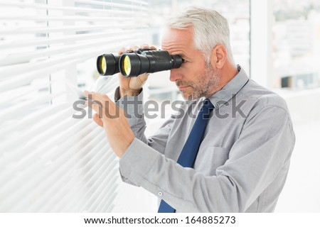 Side view of a serious mature businessman peeking with binoculars through blinds in the office