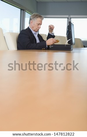 Side view of a serious mature businessman with open briefcase at conference table
