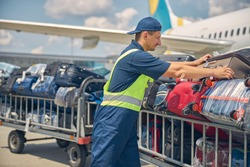 Side view of a serious young Caucasian man in uniform loading suitcases from the airplane onto the carts