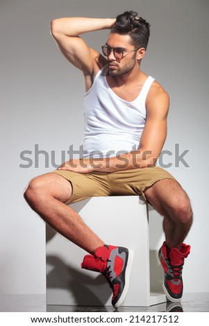 side view of a sexy fit man with hand on his head, in studio