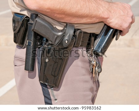 Side view of a sheriff's deputy's black patent leather duty belt with holsters and clips