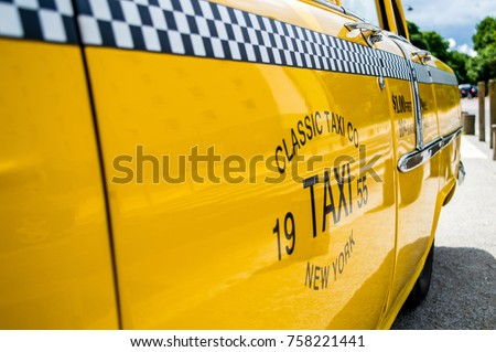 Side view of a shining yellow classic taxi with black and white grid displaying ride fare, New York, USA