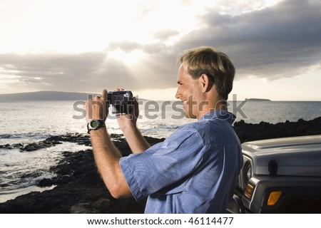 Side view of a smiling Caucasian man photographing a scenic sunset at a beach. Horizontal format.