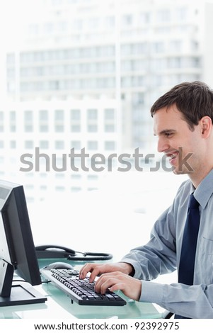 Side view of a smiling office worker using a monitor in his office
