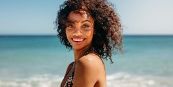 Side view of a smiling woman standing at the beach. Woman with curly hair standing on the beach with sea in the background.