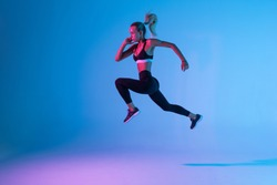 Side view of a sporty young woman jumping isolated on purple light background