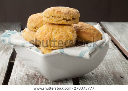 Side view of a square bowl of freshly baked homemade pumpkin muffins on an old barn wood table