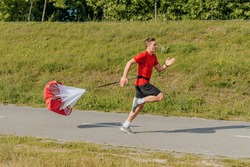 Side view of a strong man doing workout using resistance parachute outdoors