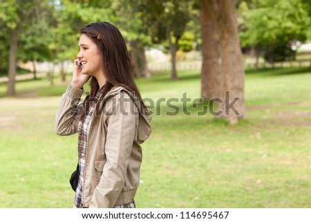 Side view of a teenager phoning in a park