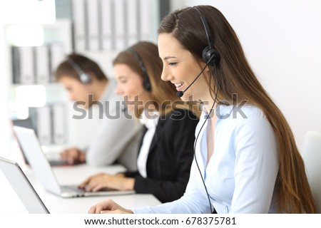 Side view of a telemarketer working on line at office with other workers in the background #678375781