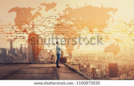 Side view of a thoughtful businessman standing on the rooftop of a skyscraper looking over the big city at sunset with a world map hologram projection. Cryptocurrency concept. Double exposure. #1100873030